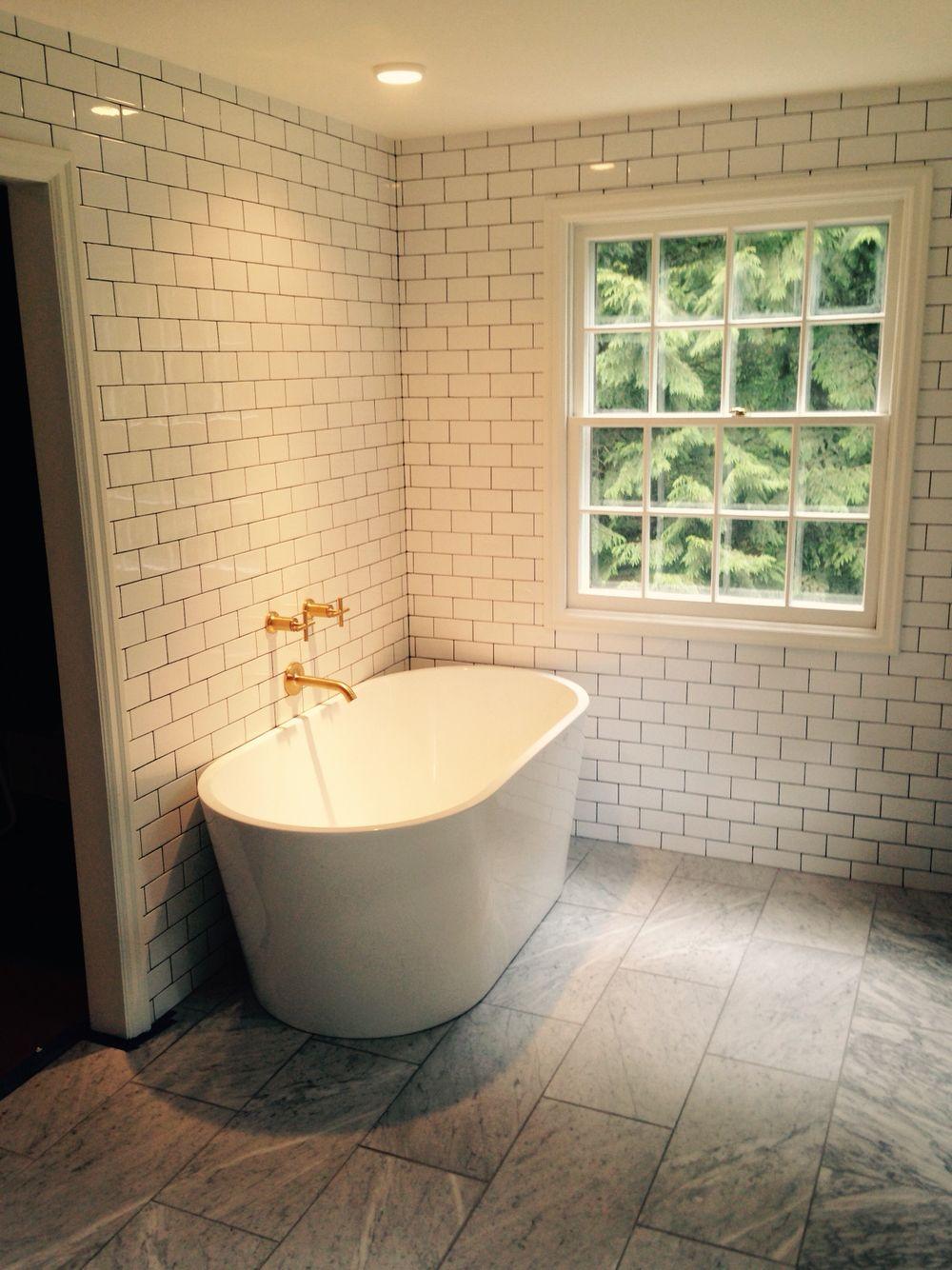 White subway tile bathroom. Freestanding tub. Brushed gold faucet ...