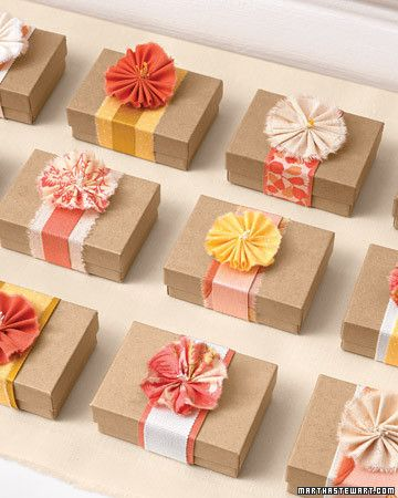 Do guests a favor and present them with tokens of affection that you've planted inside these petite flower-topped boxes. Wrap each small box with a belt of layered ribbons or a strip of woven fabric, and cap it off with a single fabric blossom.