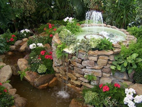 springbrunnen aus stein mit wasserspiel im garten umgeben von pflanzen garden pinterest. Black Bedroom Furniture Sets. Home Design Ideas