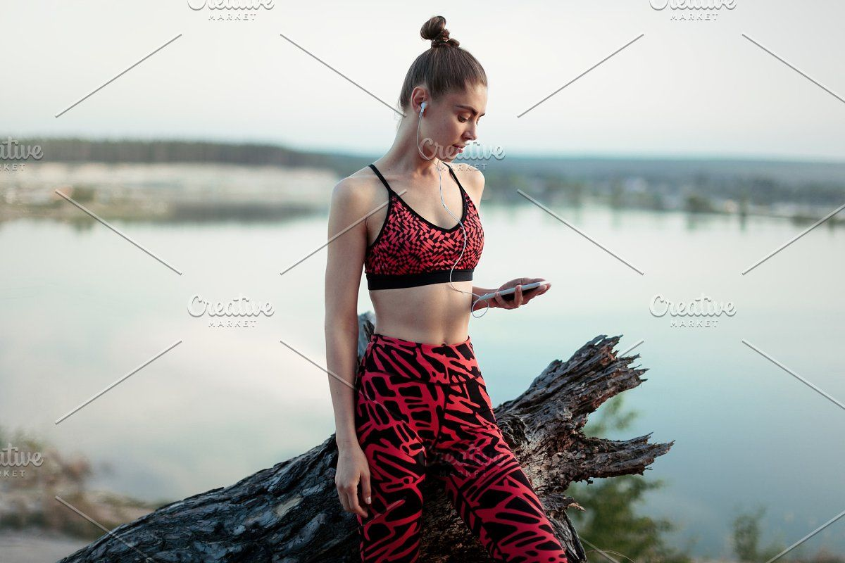 fitness girl with a smartphone on nature background, enjoys sports training, workout #Sponsored , #s...