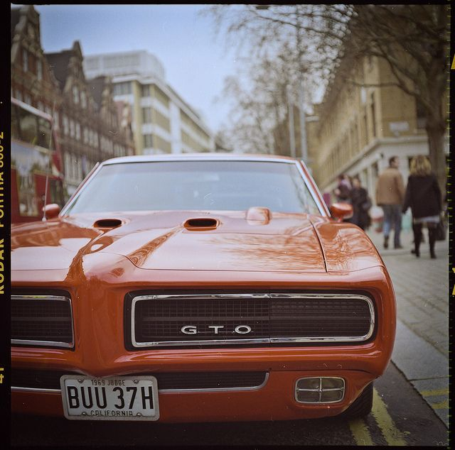 Teen pictures by a muscle car