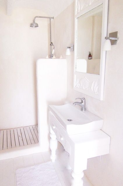 Compact shower stall. A mini shower stall with a partial wall is ...
