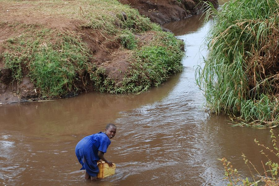 A girl leans into a dirty stream to collect water for her family in Namalu, Eastern Uganda. Millions lack access to clean water and adequate sanitation facilities which is a major contributor to deaths and illnesses of both infants and adults.