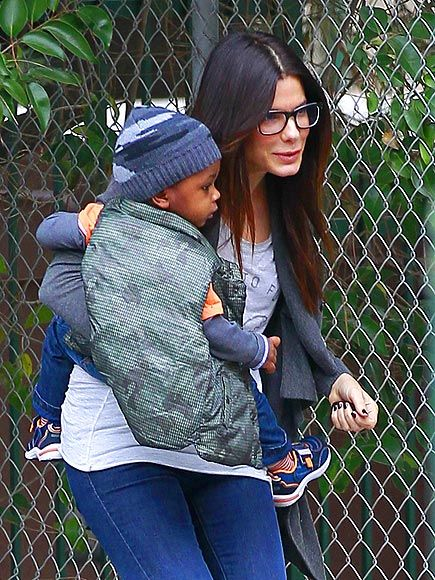 Sandra Bullock looks uber cute in her geek chic specs with her cutest accessory by her side!