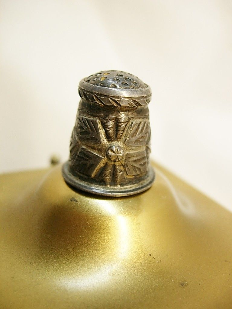 "This 1930's sterling thimble has a really odd symbol that looks like an indian dragonfly or butterfly? The other side has a diamond shield that might have been made for an initial. Originally, thimbles were used solely for pushing a needle through fabric or leather as it was being sewn. Since then, however, they have gained many other uses. In the 19th century they were used to measure spirits, which brought rise to the phrase ""just a thimbleful"". Prostitutes used them in the practice of ..."