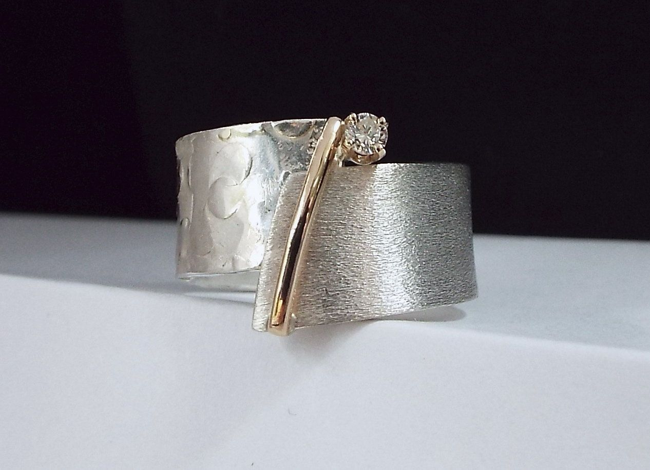 Celebration by Dagmara Costello. Handmade, hammered and textured sterling silver ring accented with 14kt yellow gold and round cut 0.08 ct diamond set in four prong yellow gold head. Ring is available in whole and half sizes 4-14. Limited edition of 30.