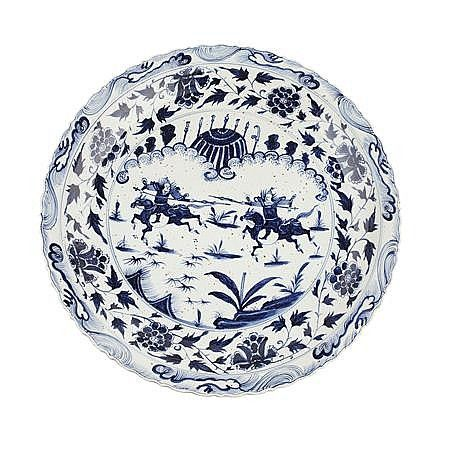 IMPRESSIVE AND LARGE BLUE AND WHITE MING STYLE CHARGER centrally decorated with two warriors on horseback within a border of foliate scrolls and lotus blossoms , the narrow barbed rim decorated with wave motifs, unmarked 78cm diameter