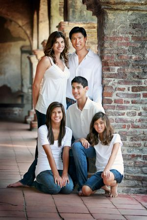 A photo of a family leaning up against a pillar, wearing