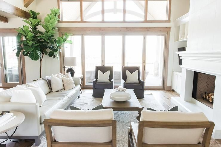 Two Story Living Room Boasts An Off White Leather Sofa With Dark Gray Wingback Chairs Me White Living Room Chairs White Leather Sofas Transitional Living Rooms #off #white #sofa #living #room