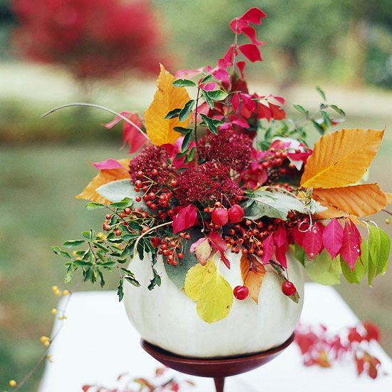 A hollowed-out holiday pumpkin makes an artsy vase for colorful flowers.