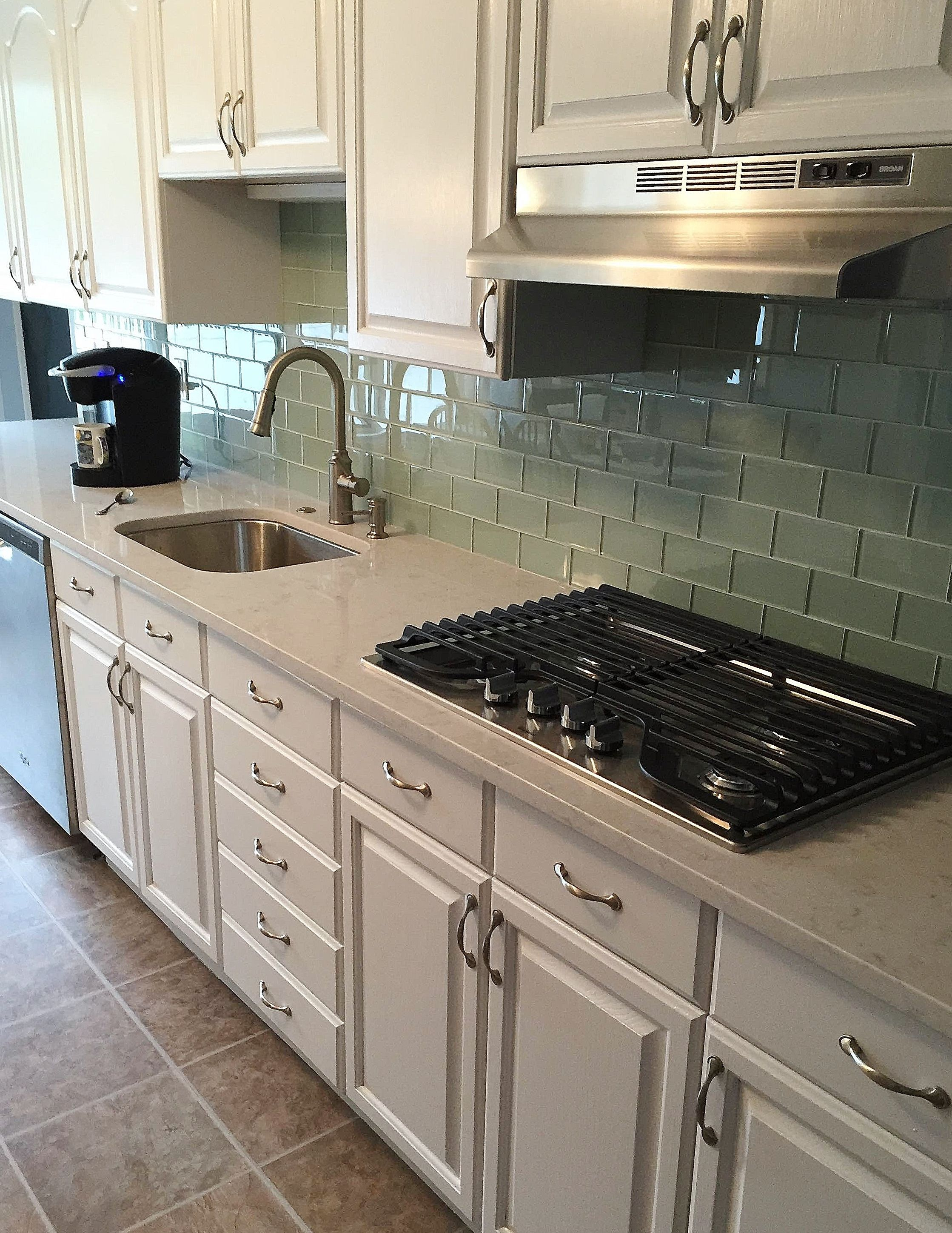silestone lagoon quartz countertops with a soft blue glass tile backsplash kitchen by stoneshop from