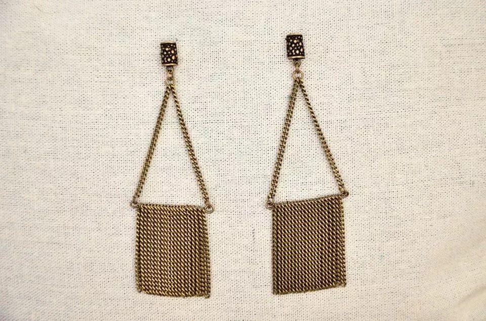 A simetria das formas e a simplicidade são o charme deste modelo todo em correntes ouro velho. Vai bem em qualquer produção. Pode ser feito também com corrente prateada.
