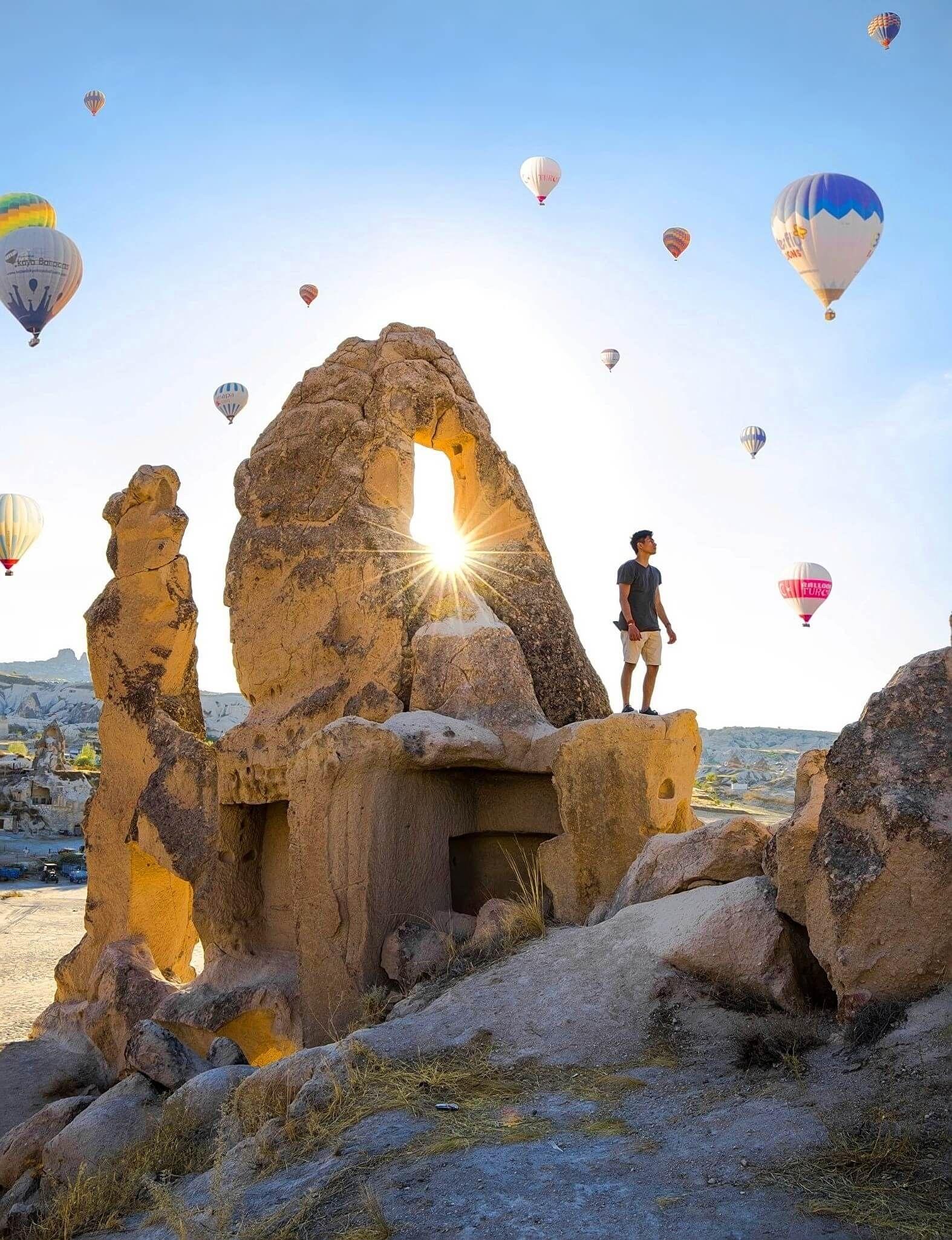 Man standing under balloons. Cappadocia, Turkey