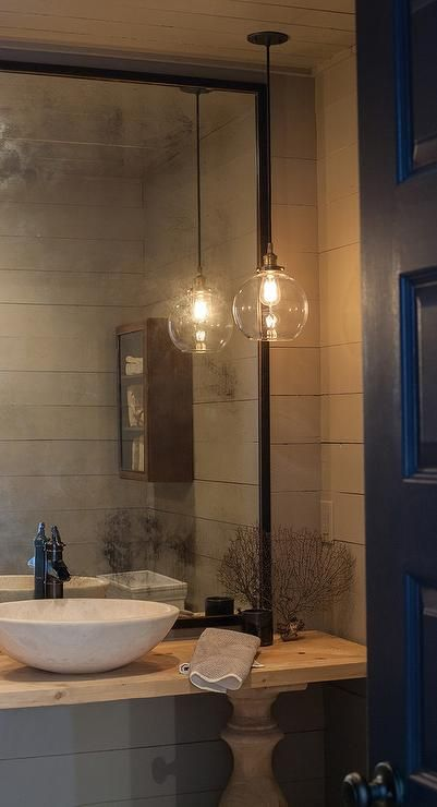 A black door opens to a gray powder room features walls clad in gray shiplap lined with a blond wood balustrade vanity topped with a marble bowl sink and bronze faucet under a black framed mirror lit by a single glass globe pendant.