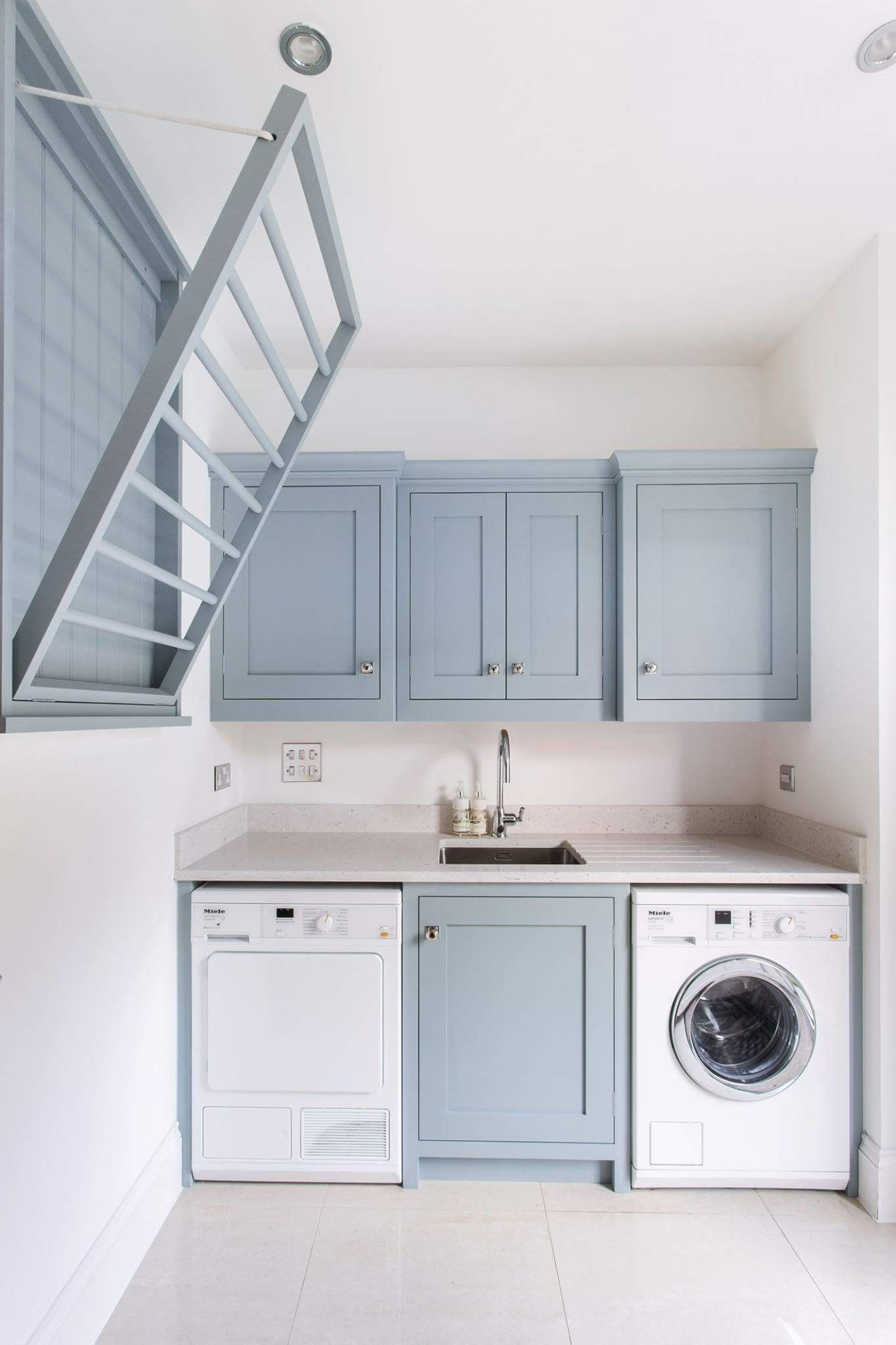 Photo of Bright laundry room with pale blue cabinetry and collapsible drying rack | NONAG…