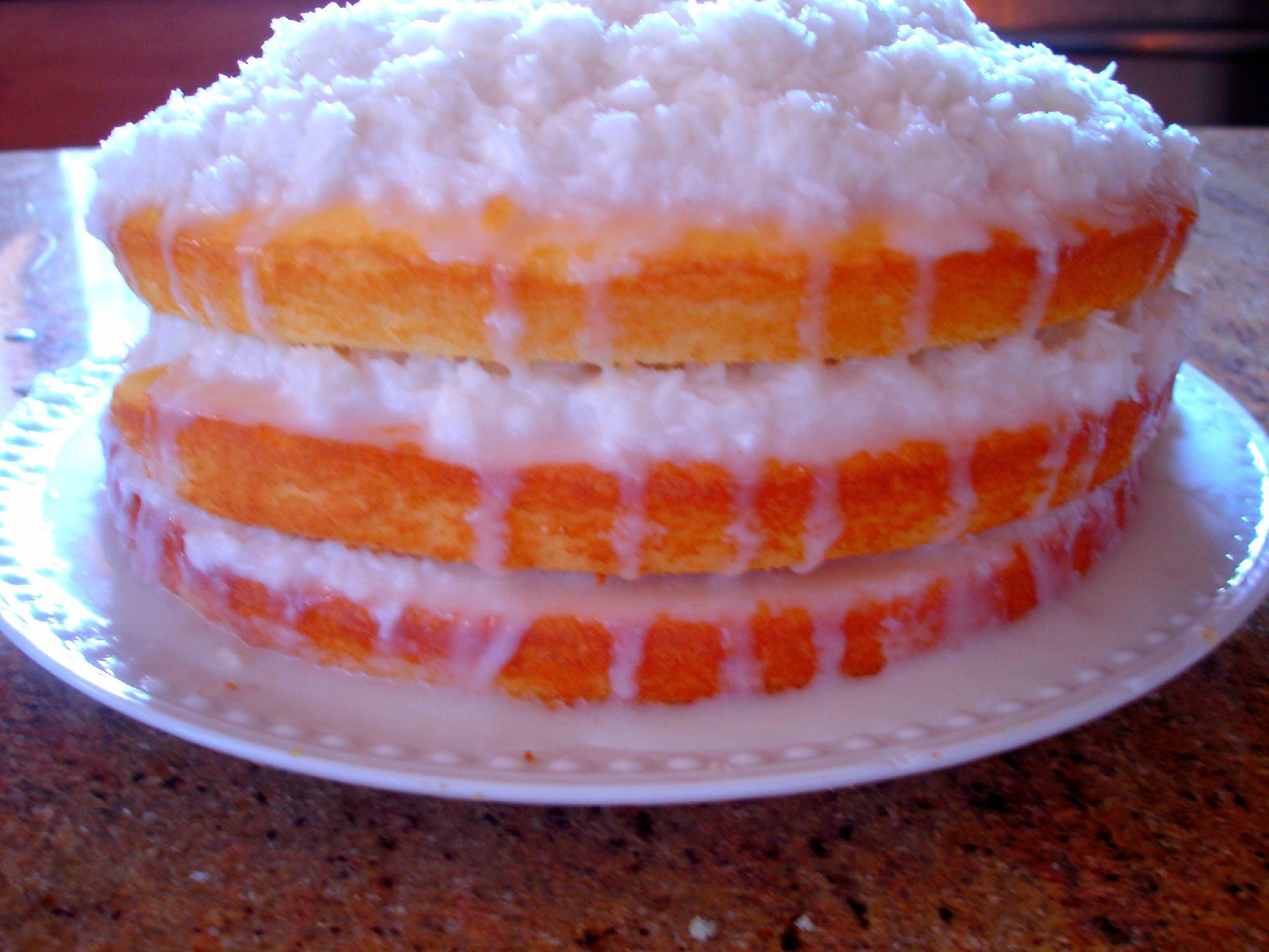 Coconut cake with sour cream filling syrup and biscuits