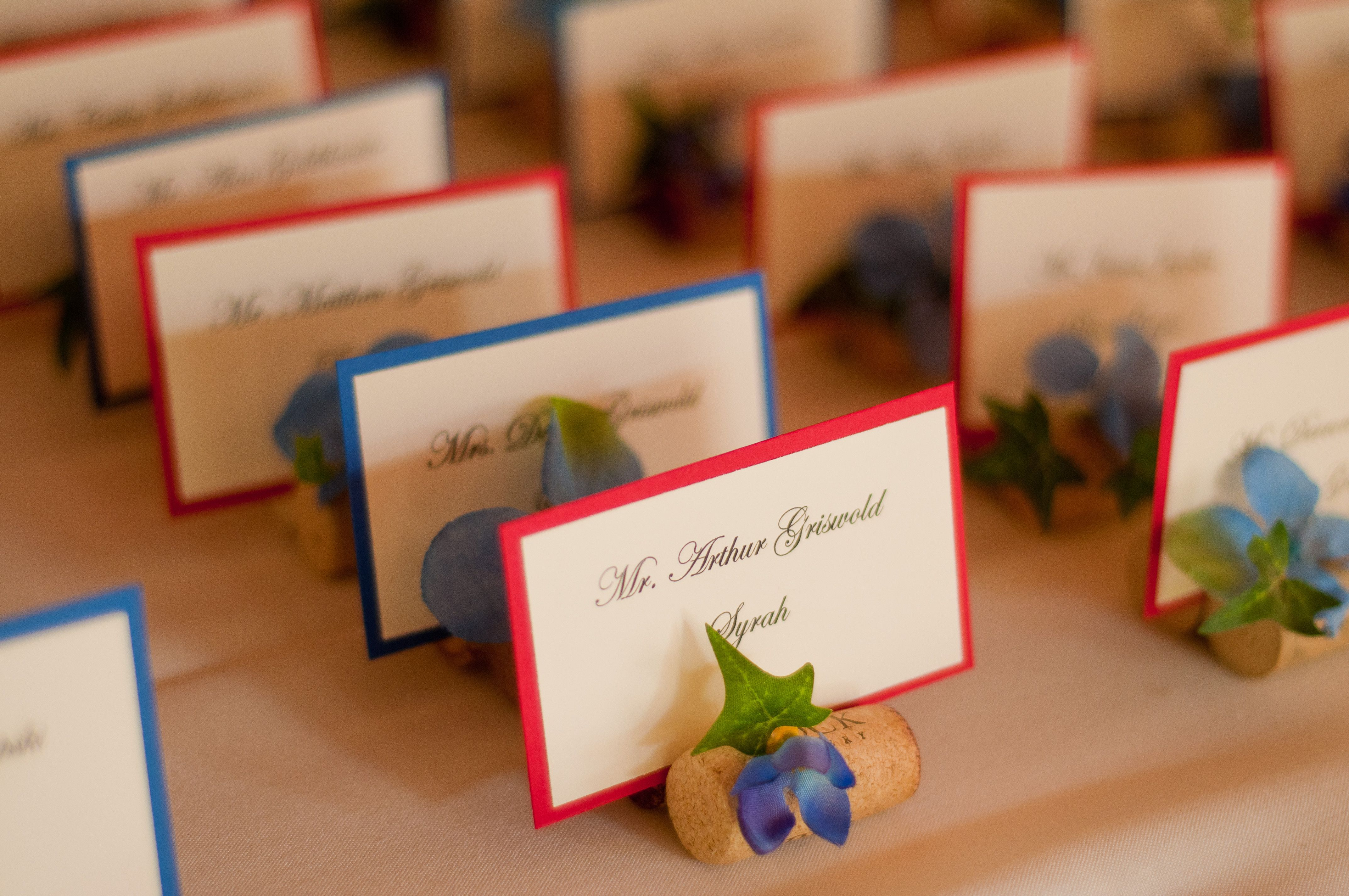 We made these place cards by gluing two corks together, adding fake flowers, and printing off the names from ivory business card paper and pasting it to colored card stock