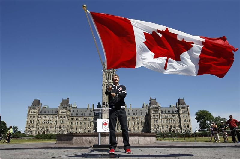 Triathlete Simon Whitfield waves the Canadian flag after being named Canada's flag bearer for the opening ceremony at the London 2012 Olympic Games.