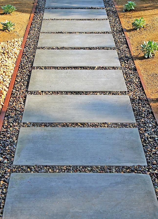 A Concrete Paver Walkway With Pebbles Is Low Maintenance