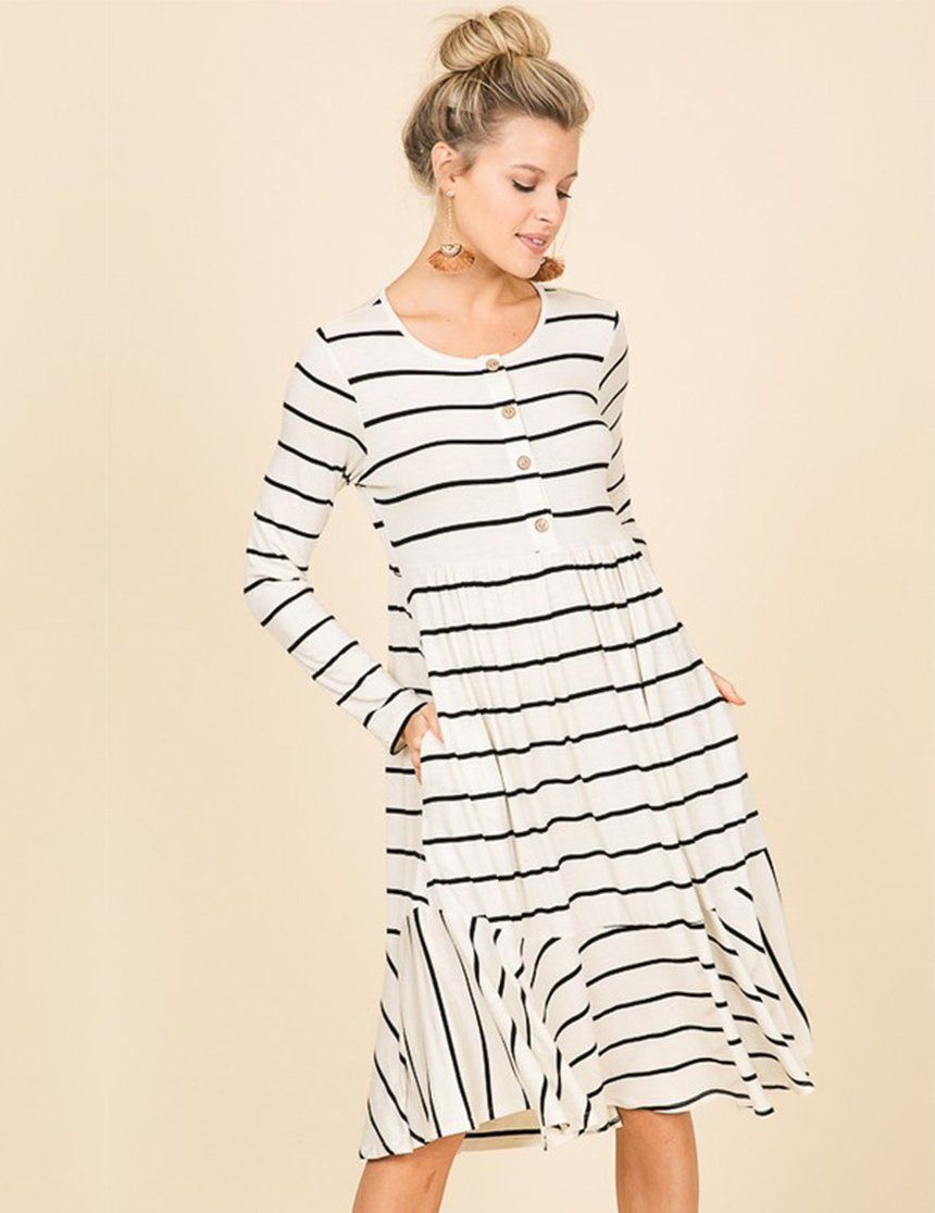 13bc0a577c6 A striped long sleeve knit dress featuring a rounded neckline, side pockets,  and a skater style hem. Functioning buttons for nursing access. Shop now.