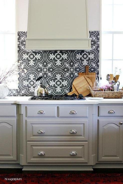 Fabulous Kitchen Features Gray Cabinets Adorned With Cup Pulls Paired White Countertops And A Black Mosaic Tile Backsplash