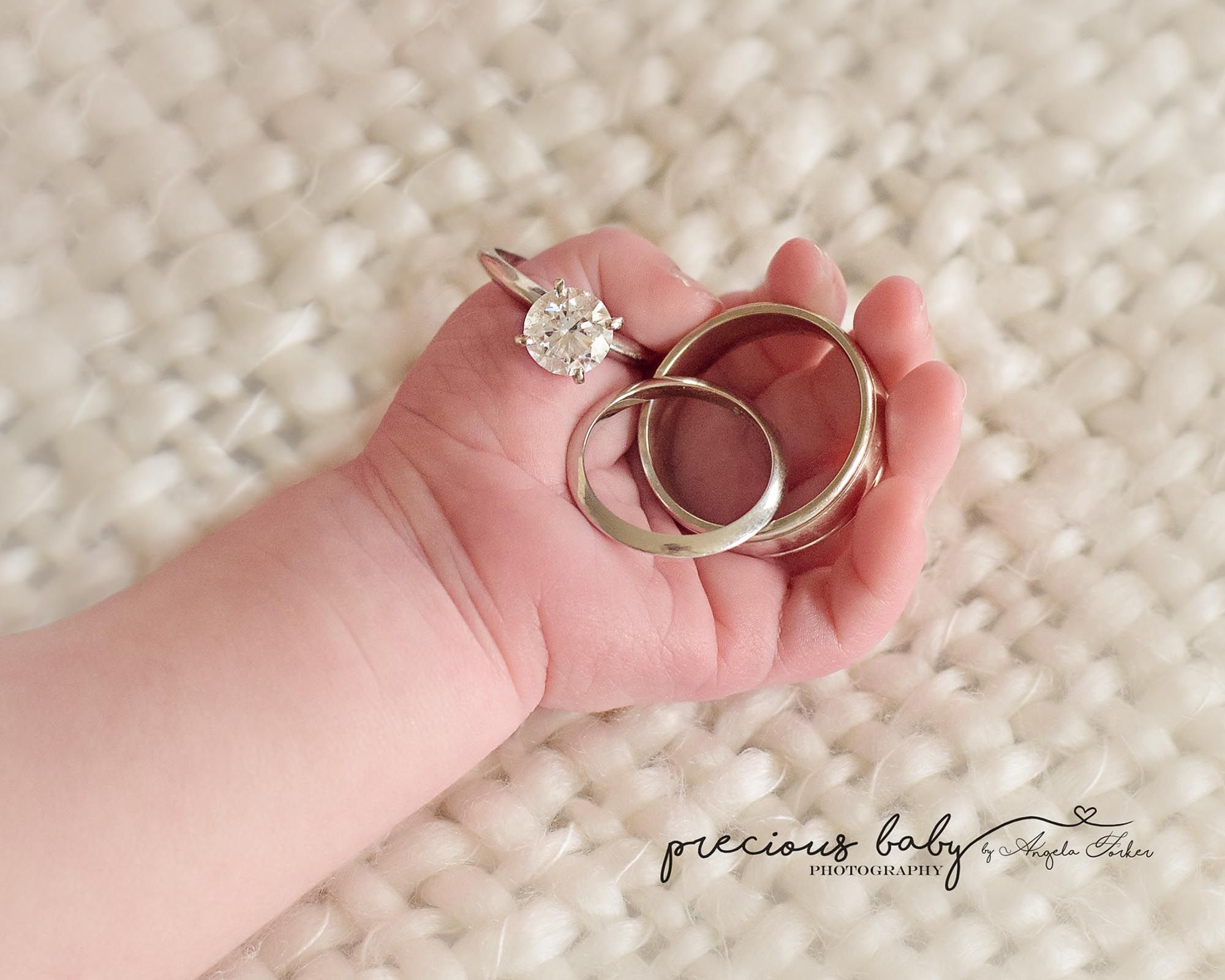 beautiful photo of newborn\'s hand holding mom and dad\'s rings ...