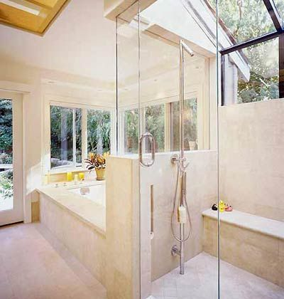 Glass shower with exposed pipes that run from floor to ceiling ...