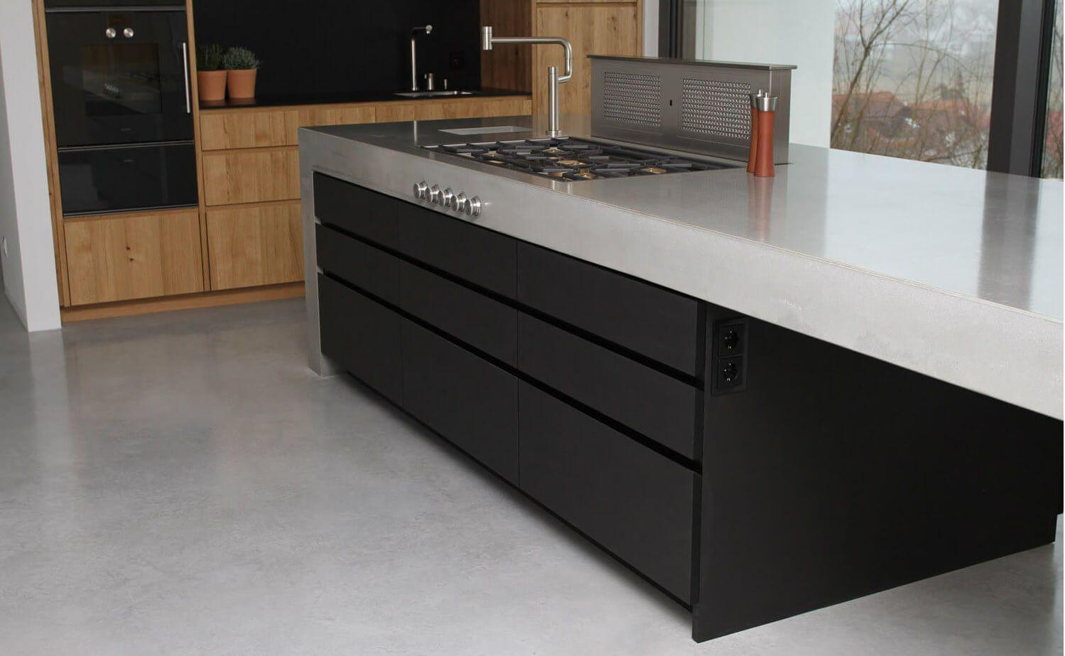 Moderne Betonküche kombiniert mit Holz und Elektrogeräten von