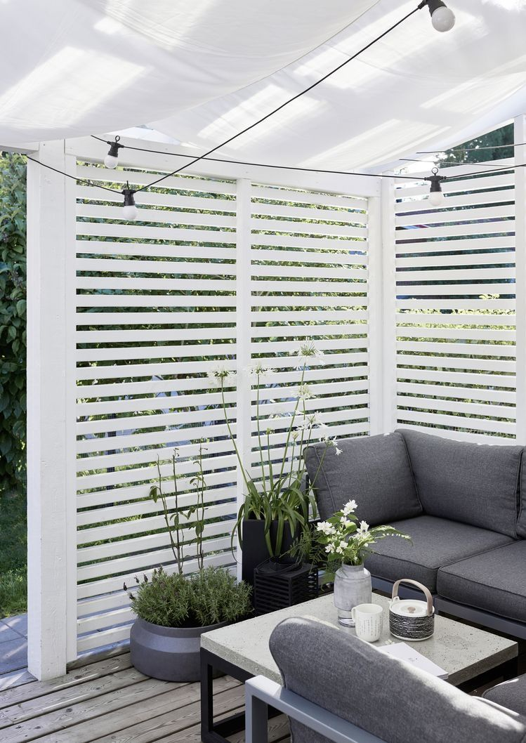 Photo of patio seating area with vertical wood slat privacy screen and white fabric sun s…