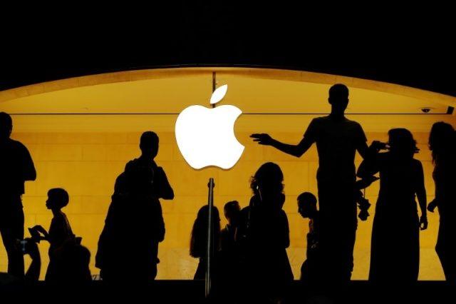 Customers walk past an Apple logo inside of an Apple store