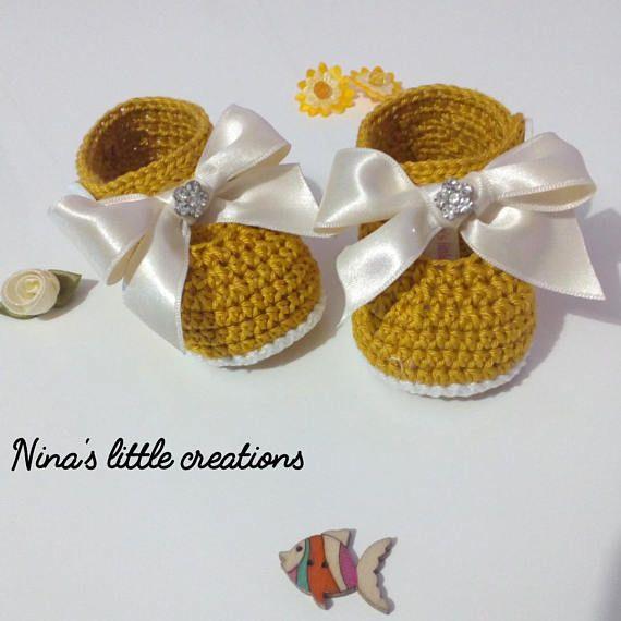 Zapatos de chica de bebé con hilo de algodón de ganchillo. El arco ...