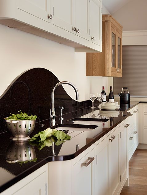 Why not try a curved backsplash? Practical and eye catching - http://www.davonport.com/kitchens/canterbury