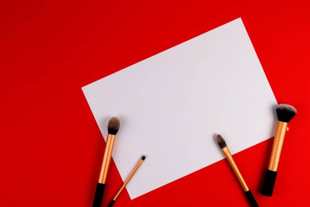 make up brushes with white blank paper on red background - blank paper background