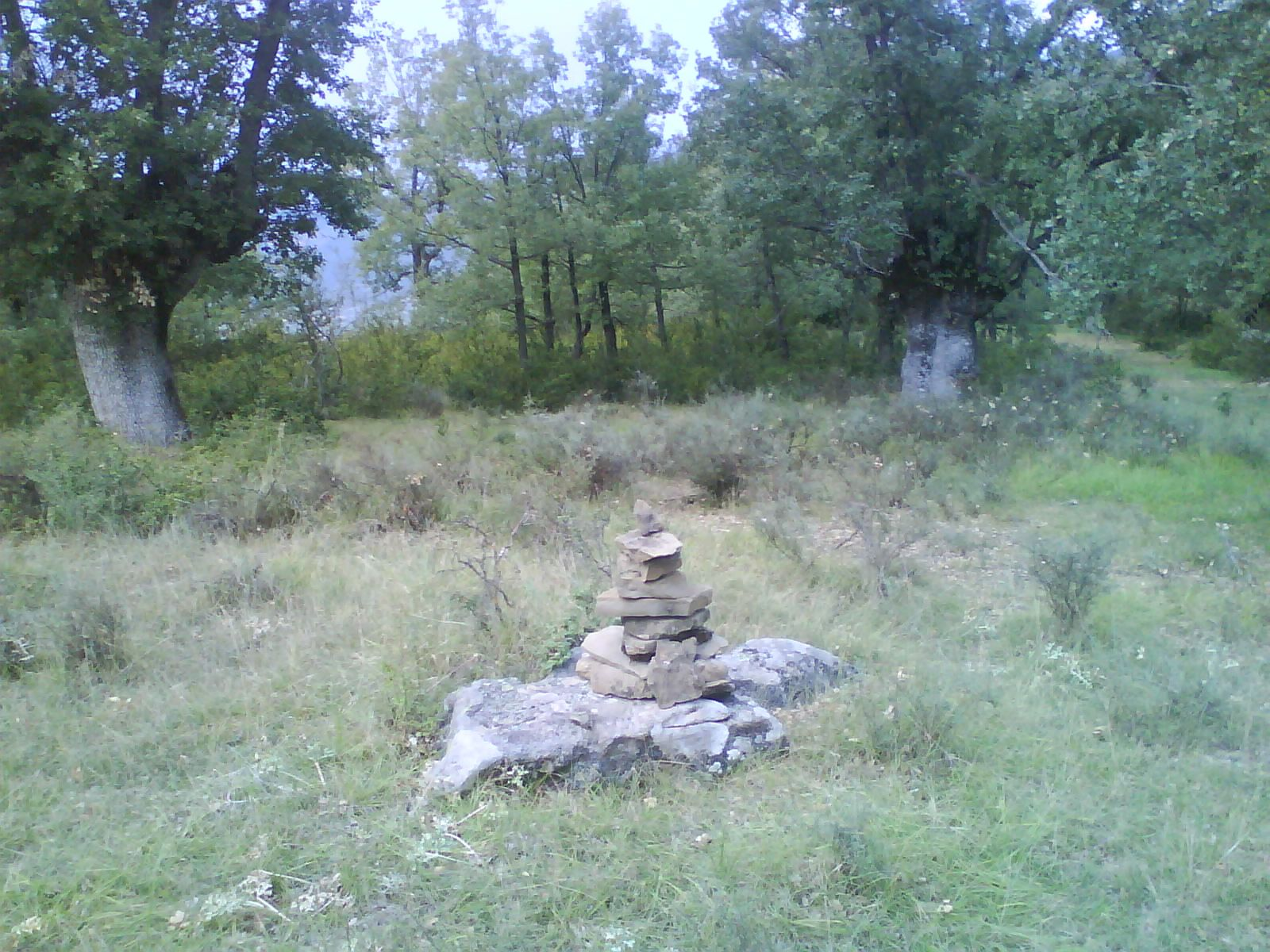 Peyrón de piedras sobre una piedra tumbada (menhir) en el caxicar de Javierre del Obispo