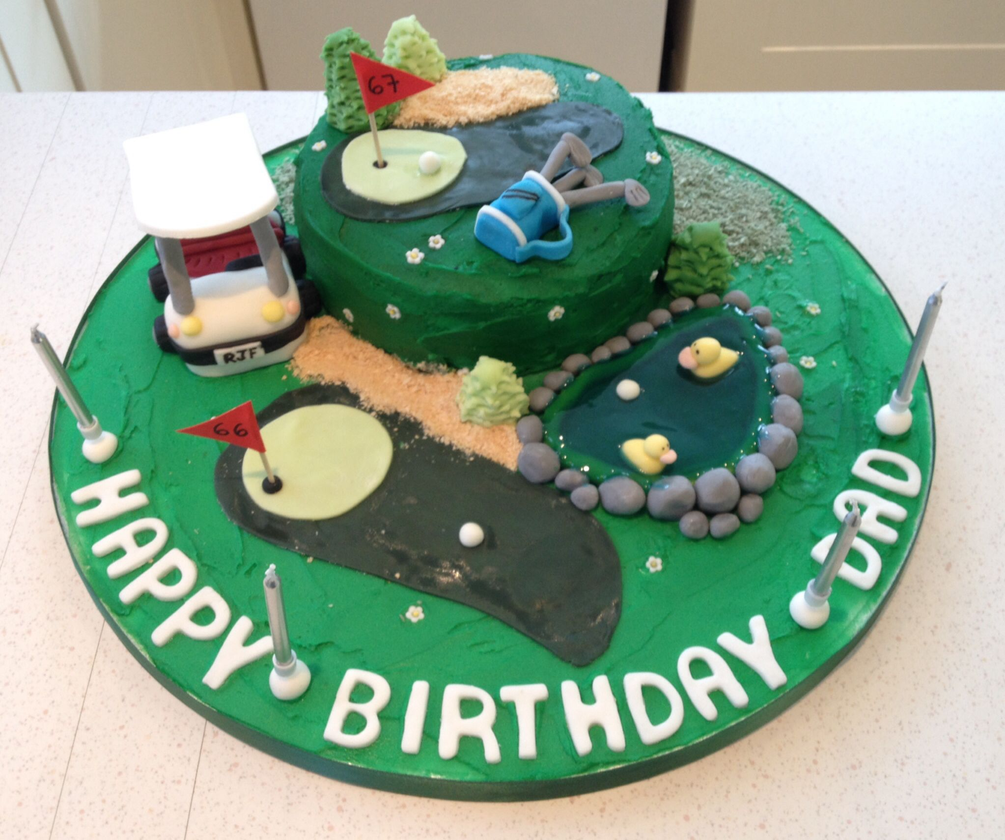 Golf cake for my dad's birthday. Fondant golf buggy & golf bag. Duck pond made with piping get and fondant rocks & ducks. Sand bunker made ice cream cones.