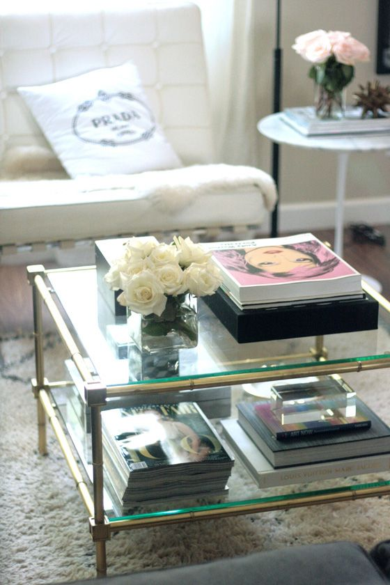 Coffee table styling: books, magazines, maybe iPads, and other stacks on the bottom; flowers and a few decorative books on top.
