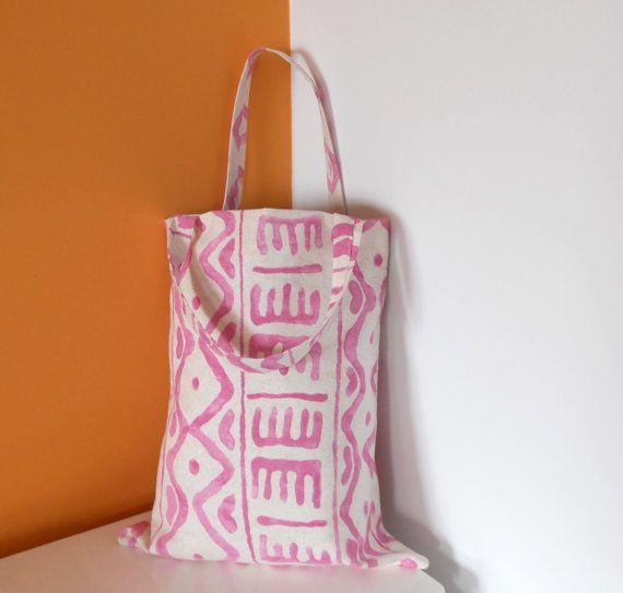 BOLSA TRIBAL  Bolsa de tela hecha a mano. El exterior está decorado con motivos étnicos en color rosa.  El interior es de color blanco e incluye una cinta rosa de raso.