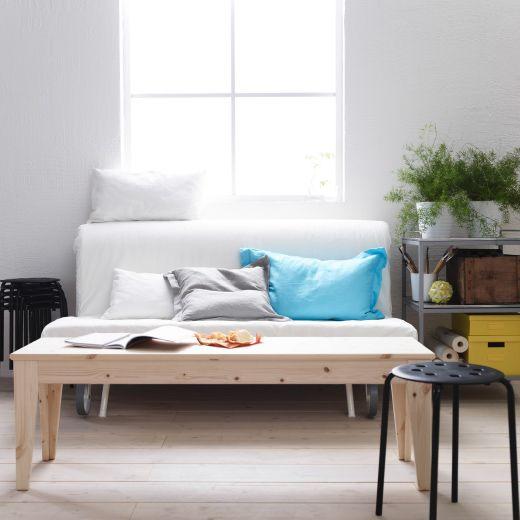 IKEA bänk i trä som fungerar som soffbord framför en bäddsoffa vardagsrum Pinterest