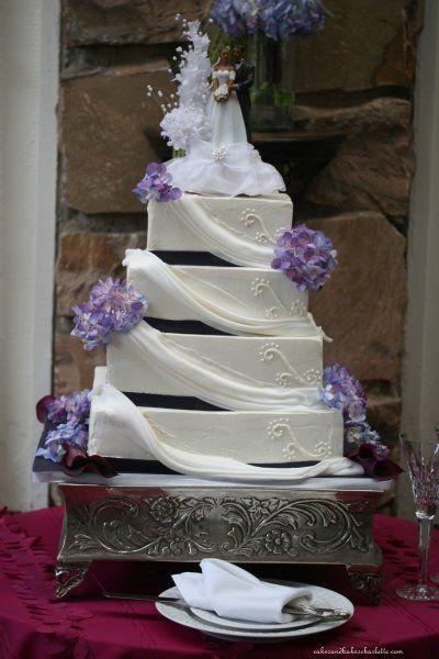 White buttercream wedding cake with fondant draping and eggplant ...