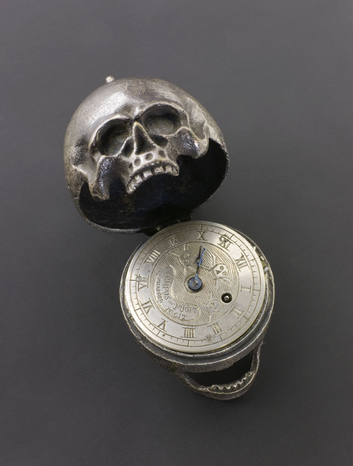 Skull Pocket Watch, Europe; 1701-1900; Silver model of a human skull which  opens up to show a pocket watch inside inscribed with skull and cross bone;  ...