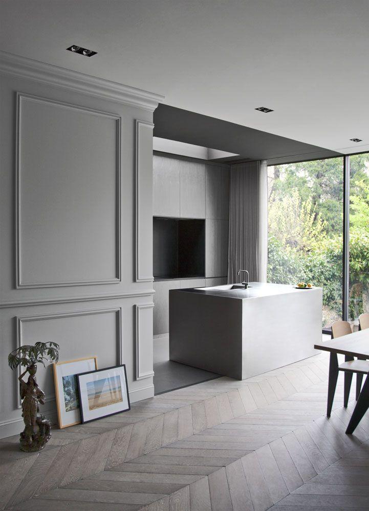 una cocina con mucha clase en tonos grises y parquet en espiga
