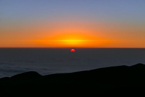 Taken from the Paranal mountain, home to the ESO Paranal site that houses the Very Large Telescope (VLT), this spectacular view points out over the South Pacific Ocean at sunset. The water itself is hidden beneath a second sea of very thin clouds — so thin that the Sun shines up through them, revealing the line of the true water horizon, giving the odd illusion that the Sun has already sunk beneath one horizon, and is preparing to set for the second time.