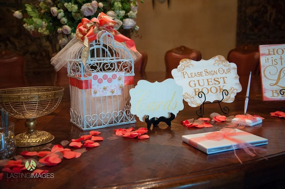 Gold wire bowl, white and pink bird cage, and guest book for sign in table with pink rose petals   Lasting Images Photography   villasiena.cc