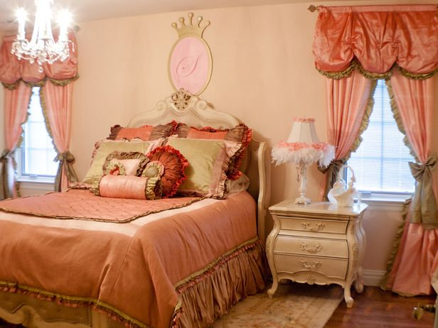 This princess-themed bedroom is pink, pink, pink.  Pink walls, pink curtains and pink bedding prove that this little girl knows what she likes.  Aside from the glamorous pink fabric, the crown above the bed, the elegant chandelier and the boa lamp make this bedroom look and feel like a royal bedchamber.  Design by Sherri Blum