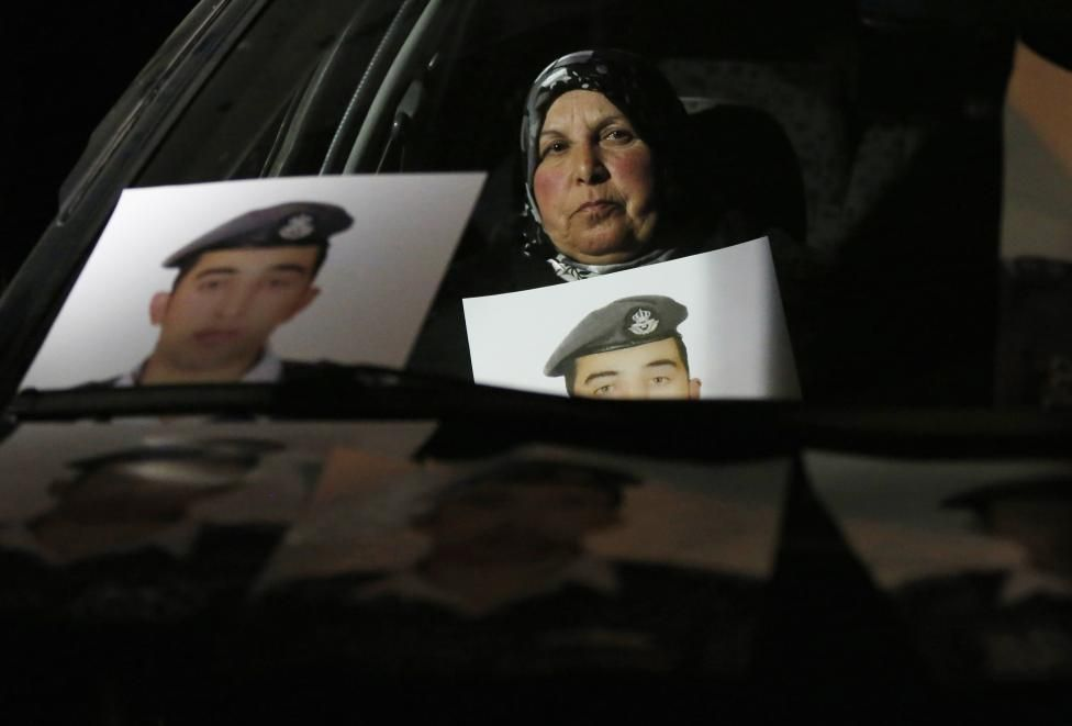 Mother of Islamic State captive Jordanian pilot Muath al-Kasaesbeh holds his picture while sitting in a car, as she takes part in a demonstration demanding that the Jordanian government negotiate with Islamic state and for the release of her son, in front of the prime minister's building in Amman, January 27, 2015. Kasaesbeh was captured after his jet crashed in northeast Syria in December during a bombing mission against the...