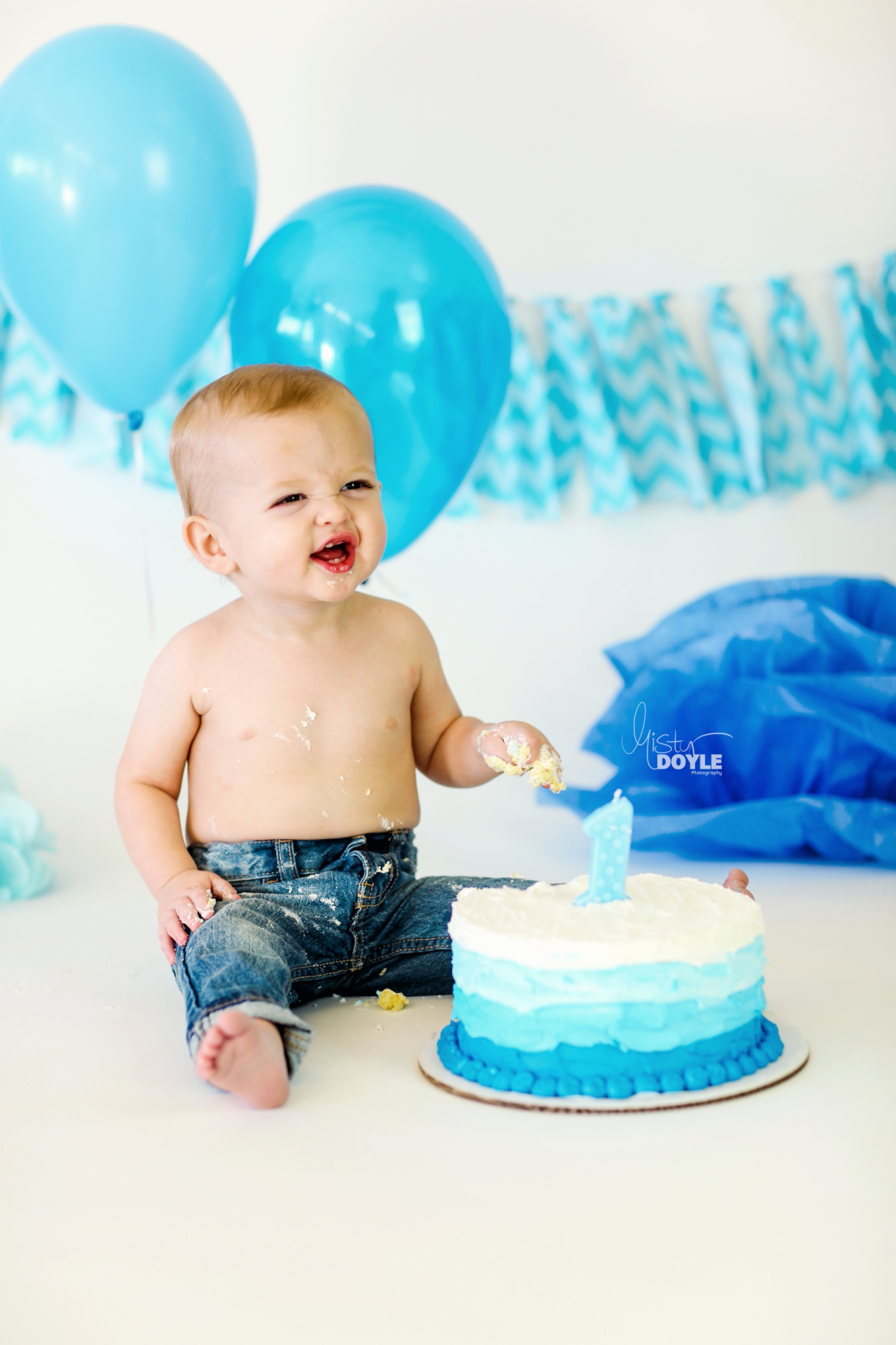 First Birthday Smash Cake Baby Boy In Jeans With Blue Ombre Fabric Banner And Balloons