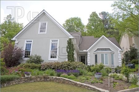 Picture Of A Nice Grey Stucco House With A Nice Flower Garden In