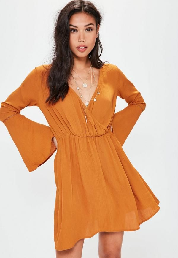 bc0dfc95db45 Add a bit of flare to your day game wearing this orange dress. Featuring -  a cheesecloth fabric, wrap plunge front and rustic undertones.