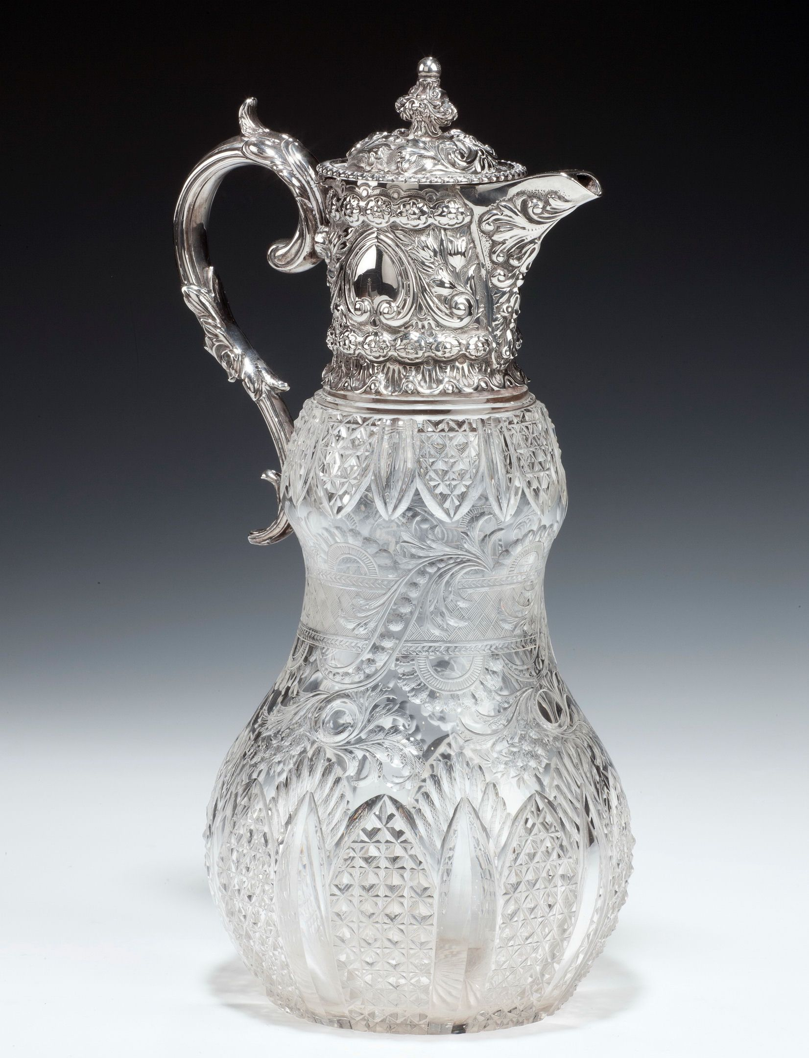 A wonderful silver claret jug, the gourd shaped body is beautifully cut and was probably made by Stevens & Williams, Stourbridge, with an ornate silver mount and handle by William Hutton & Sons Ltd.