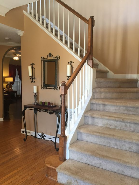Traditional Staircase With High Ceiling, Wall Sconce, Crown Molding,  Hardwood Floors